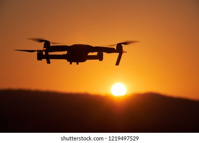 Drone flying at the sunset on red sky