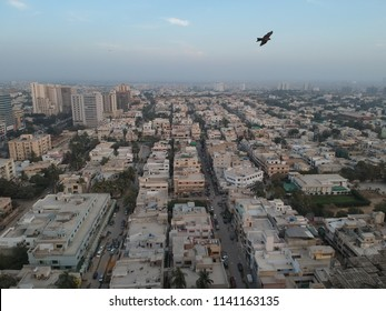 drone footage of day time karachi, a flying bird,sky,buldings ,clouds and the streets of karachi