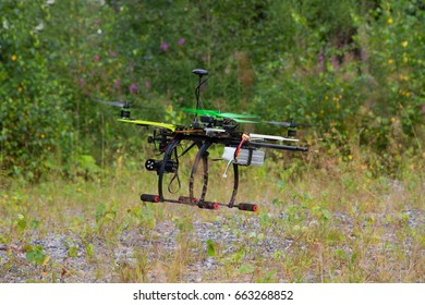 Drone with green propellers is flying in a summer day. Forest and shingle as a background.