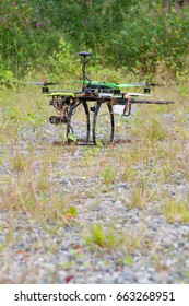 Drone with green propellers is on grass in summer day. Forest and grass as a background.