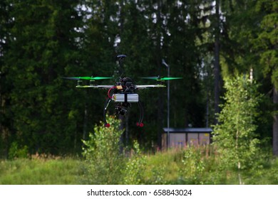 Drone with green props is flying in a bright summer day. Forest as a background.