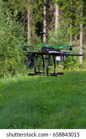 Drone with green props is flying. Summer day. Green forest and green field with small flowers as a background.