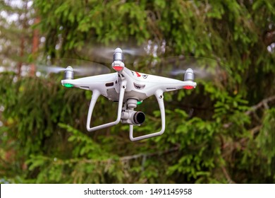 Drone hovered in background of forest. drone hovers on woodland path. drone is in mid flight and surrounded in lush pine forest. Drone is hovering in air.