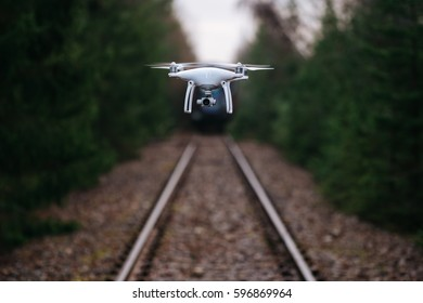 Drone hovering over railroad in the middle of the forest