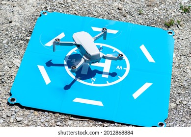 The drone hovers over the blue landing pad on the rocks, the plastic propellers are on, a visible USB slot and a memory card. - Shutterstock ID 2012868884