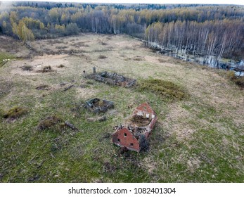 drone image. aerial view of rural area with fields and forests, old house ruins in cloudy spring day. latvia