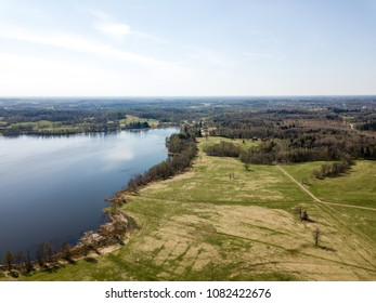 drone image. aerial view of rural area with countryside lake enclosed by fields and forests. sunny spring day. latvia