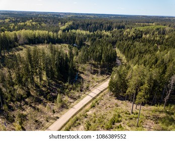 drone image. aerial view of rural area with fields and forests and gravel roads seen from above. latvia