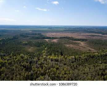 drone image. aerial view of rural area with fields and forests and swamp lake with blue water. latvia