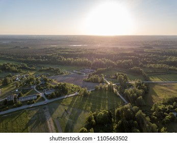 drone image. aerial view of rural sunset over forest trees with long shadows. latvia