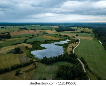 drone image. aerial view of rural area with houses and roads under heavy and dark dramatic rain clouds in summer day. night photo. latvia