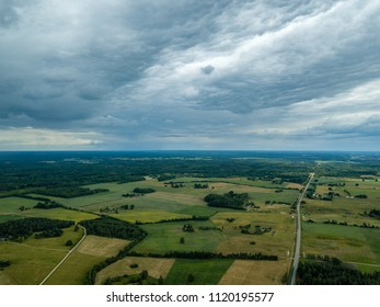 drone image. aerial view of rural area with houses and roads under heavy rain clouds in summer day. latvia