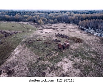 drone image. aerial view of rural area with fields and forests, old house ruins in cloudy spring day. latvia - vintage film look