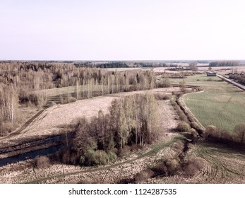 drone image. aerial view of rural area with fields and forests in cloudy spring day. latvia - vintage film look