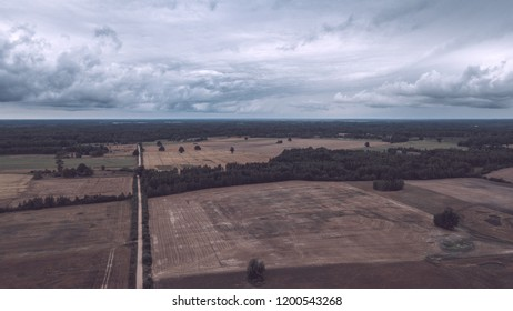drone image. aerial view of rural area with fields and forests under dramatic storm clouds forming. summer day in latvia - vintage retro look