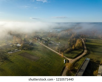 drone image. aerial view of rural area with fields and forests covered in autumn mist. latvia