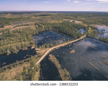 drone image. aerial view of rural area with fields and forests and water reflections in river in cloudy spring day. latvia - vintage old film look