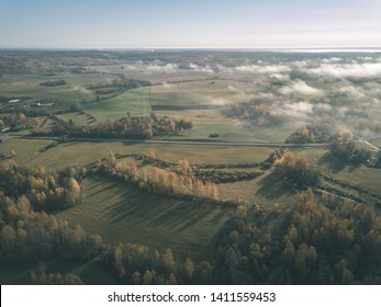 drone image. aerial view of rural area with fields and forests covered in autumn mist. latvia - vintage old film look