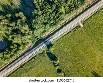 drone image. asphalt road surrounded by pine forest and fields from above in latvia