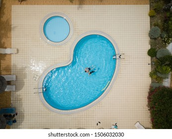 Drone image, birds eye view about a blue swimming pool, with playing children