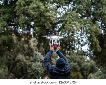 A drone landing in the hands of a man in the forest