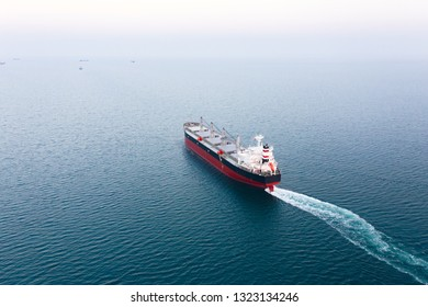 Drone large speed sea vessel for transporting a cargo ship at high speed leaves the city sea port to open blue sea space at sunset. Import, export of goods by sea