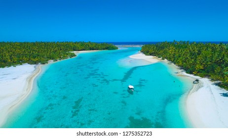 DRONE: Locals anchor their boat and jump into the refreshing turquoise colored ocean water surrounding the remote tropical island in the Pacific. People enjoying their vacation on One Foot Island.