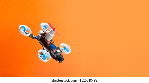 Drone multicopter with camera on orange background. Creative design aerial robotic rotorcraft mechanism 5 propellers, copy space