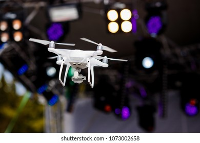 Drone on radio control fly and takes photos and video of concert on stage under spotlights.