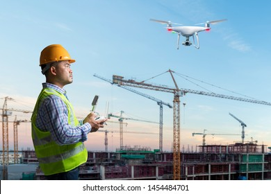 Drone operated by construction foreman for survey and checking working on top floor of high building construction site in sunset