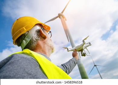 Drone operated by construction worker inspecting wind turbine, flying with drone.