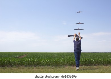 Drone operator launches the fixed wings drone above a soybean field