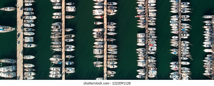 Drone panoramic birds eye view yachts motorboats sailing ships nautical vessels docked in a row at port of Torrevieja town. Aerial of marina and green bay of Mediterranean Sea. Alicante province, Spai