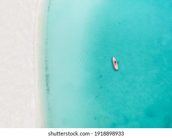 Drone photo of beach in Grace Bay, Providenciales, Turks and Caicos. The caribbean blue sea and underwater rocks can be seen, as well as some jet skies
