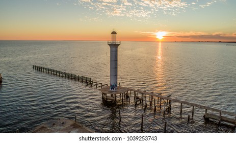 Drone photo overlooking a lighthouse in Biloxi Bay during sunset.