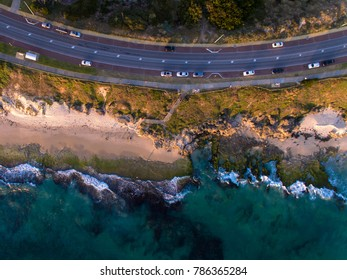 Drone photo of the road next to the rocky reef coastline at North Cottesloe, Perth, Western Australia. Cars parked next to the ocean.