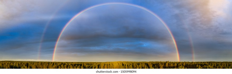 Drone photo of the whole rainbow over summer pine tree forest, very clear skies and clean rainbow colors. Scandinavian nature landscape under  evening sun. Rainbow is double in the most of photo