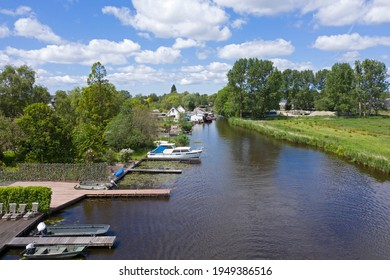 Drone photo of a wide ditch with boats on a jetty and green trees and grassland on a sunny day in spring. Photo taken in Landsmeer, Holland
