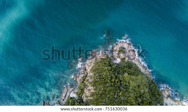 Drone photograph of a coastline with waves crashing against the rocks with trees on it. Crystal clear water.