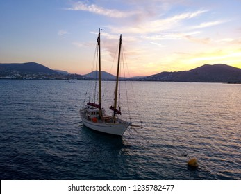 A drone picture of a boat is at the sunset in Paros island, Greece.