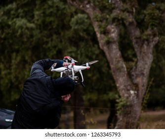 A drone pilot configuring his drone in the forest before flying