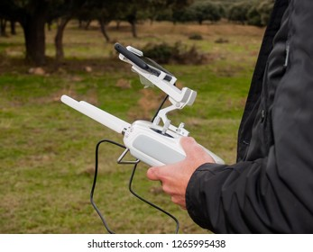 A drone pilot piloting with the remote control with smartphone in his hands in the forest