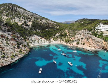 Drone point of view aerial photo moored yachts on the bright blue bay on the Cala Blanca Andratx in the Palma de Mallorca, rocky coast breathtaking view, Balearic Islands Spain