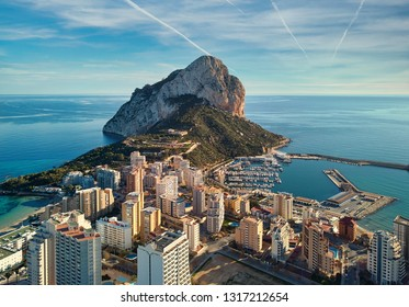 Drone point of view Rock of Penon de Ifach, harbor, Mediterranean sea rooftops of houses Calp cityscape. Coastal town located in comarca of Marina Alta province of Alicante Valencian Community, Spain