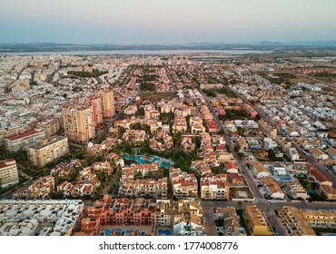 Drone point of view spanish resort townscape of Torrevieja during sunset evening light. Aerial photography residential district houses rooftops view from top. Costa Blanca, Province of Alicante, Spain