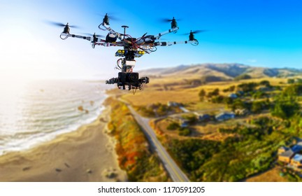 Drone with professional cinema camera flying over Pacific Ocean and the mountains in California