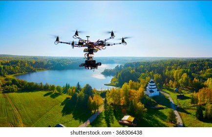 drone with professional cinema camera flying over a autumn park in fall colors under morning light with deep long shadows