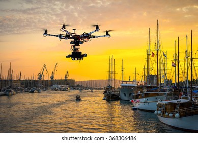 Drone with professional cinema camera flying over the bay with yachts in the summer at sunset