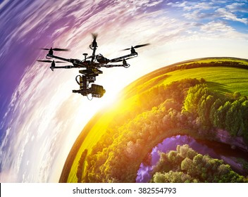Drone with professional cinema camera flying over a blue calm river in the forests and fields at the sunset. Hexacopter drone with high resolution digital camera on the sky. Little planet effect.