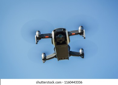Drone with propellers flies in the sky and photographs terrain
